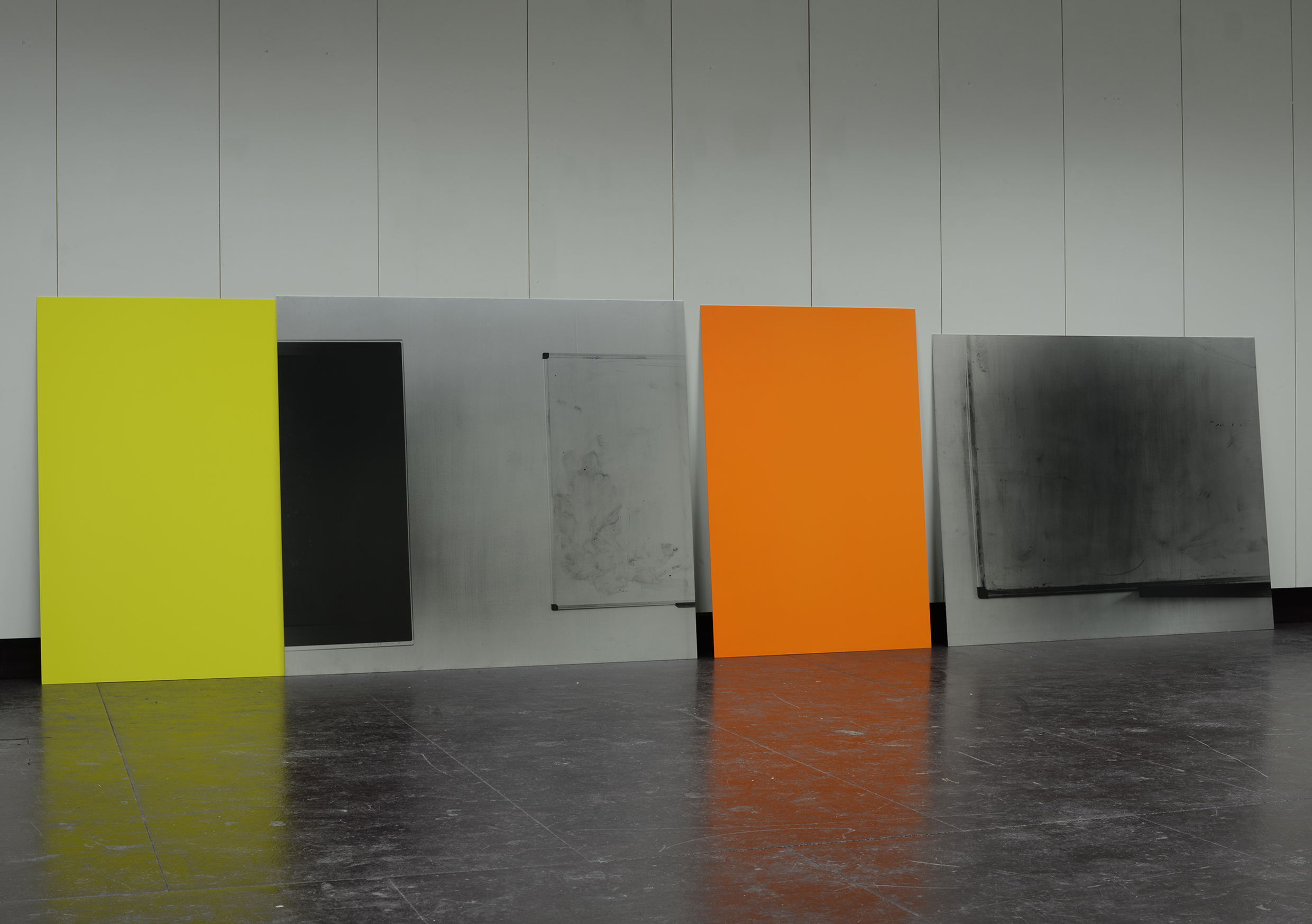 "Display of four visual works by Mary Maclean leaning against a wall. Titled ""Extremely"" by Mary Maclean"