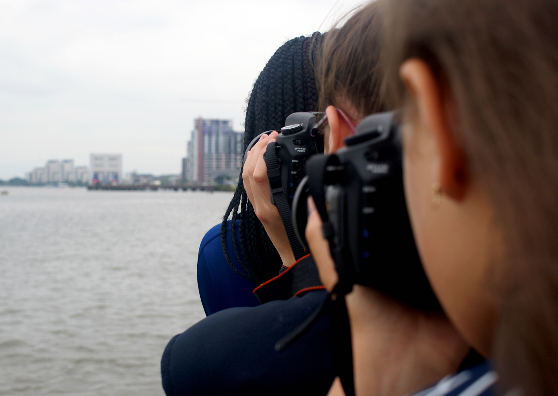 Photograph of three people using cameras to take pictures at the same landscape