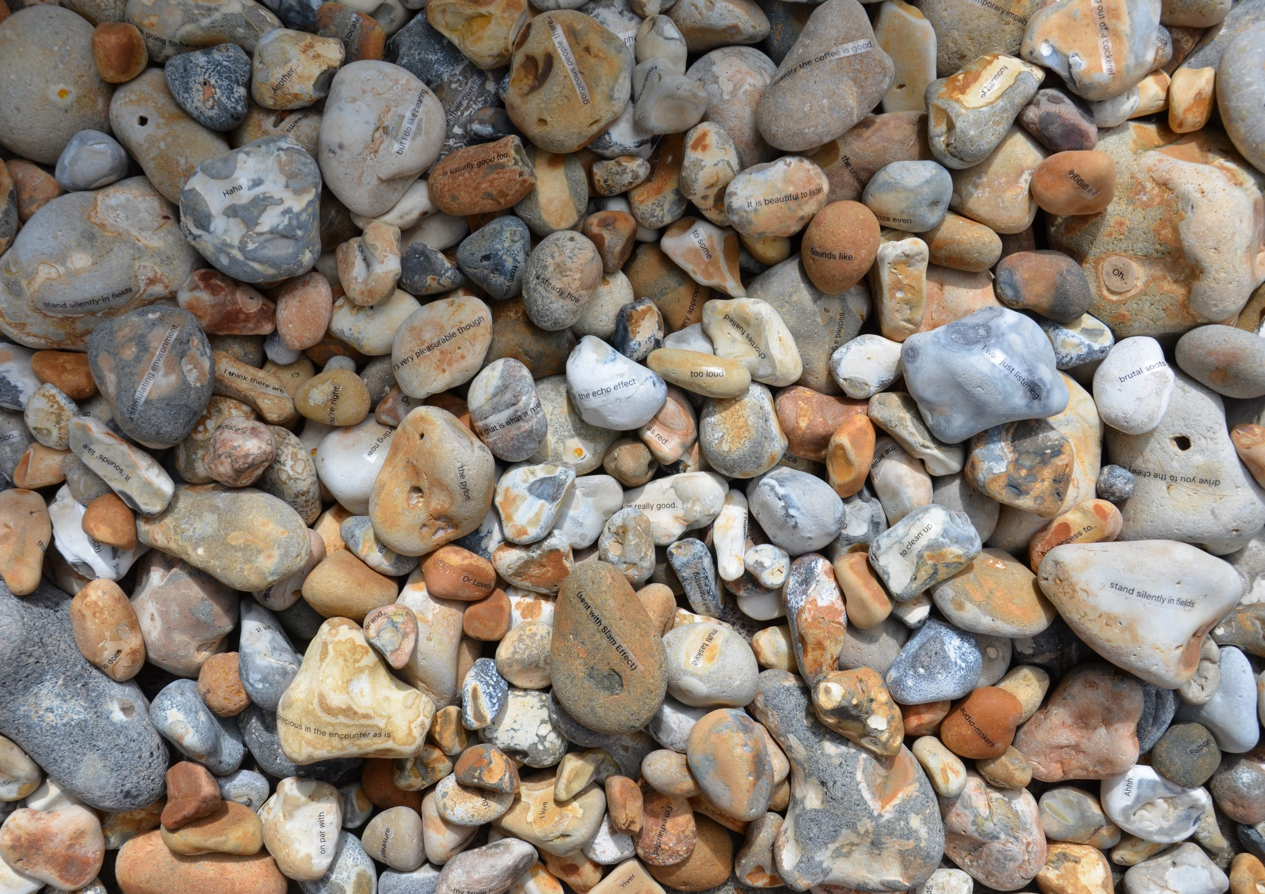 Universal Crepitation Featured Image - Photograph of stones with text on them, light shining on them from the right